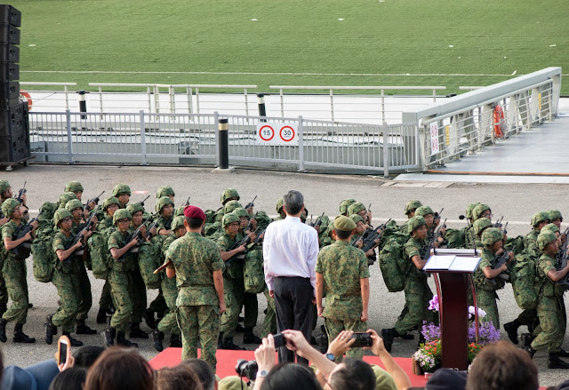 soldiers marching past podium