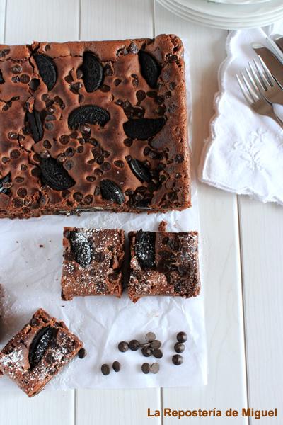 Foto panorámica del brownie sobre papel de horno también hay cortadas tres porciones con azúcar glass y pepitas de chocolate todo sobre una mesa de madera blanca , a la derecha una servilleta blanca con dos tenedores.