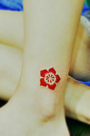 bright red totem flower tattoo on the ankle