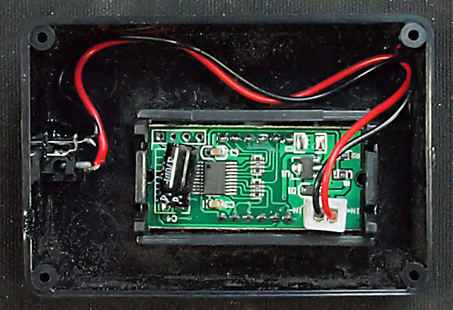 Inside the box showing the back of the voltmeter and the back of the DC power socket to the left.