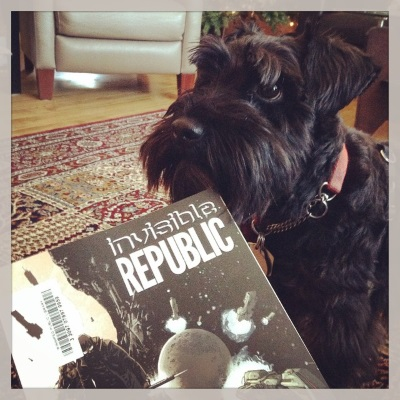 A black mini schnauzer, Duffy, stands staring upwards at something outside the frame. In front of him is the edge of a trade paperback copy of Invisible Republic Volume One. The primarily black cover features two pale-skinned people arrayed against a galactic montage.
