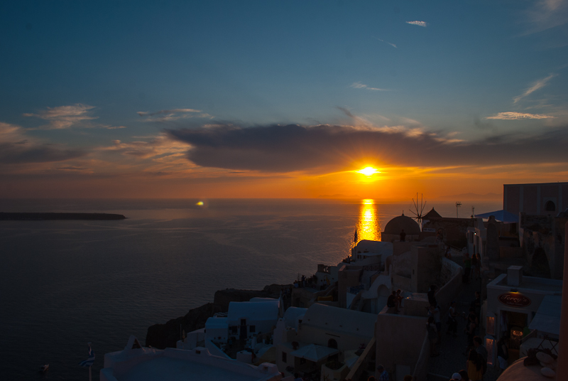image of the sun setting in oia santorini