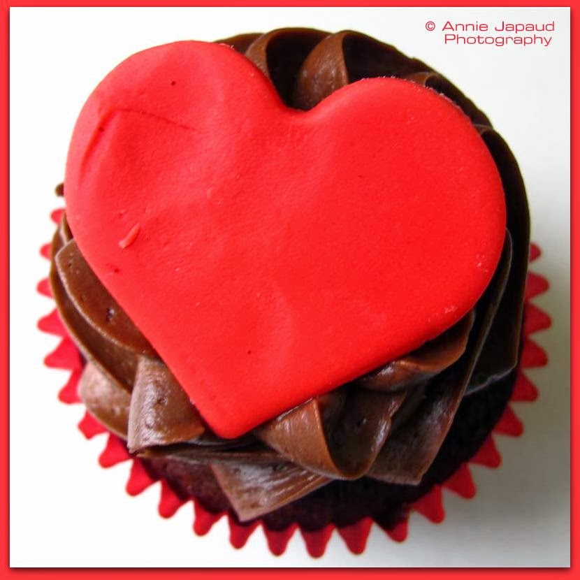 an image of a cup-cake with red heart decoration and chocolate cream piping