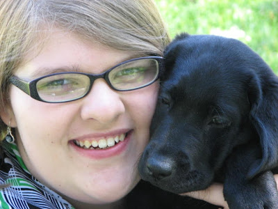 Taelor Michehl with black Lab puppy