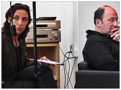 Links spricht eine Dolmetscherin, die hinter dem Ständer eine Lampe sitzt, den Stenoblock in den Händen, rechts hört in einem Sessel sitzend ein Mann konzentriert zu, Stichwort: Dolmetschen bei Dreharbeiten in Berlin.