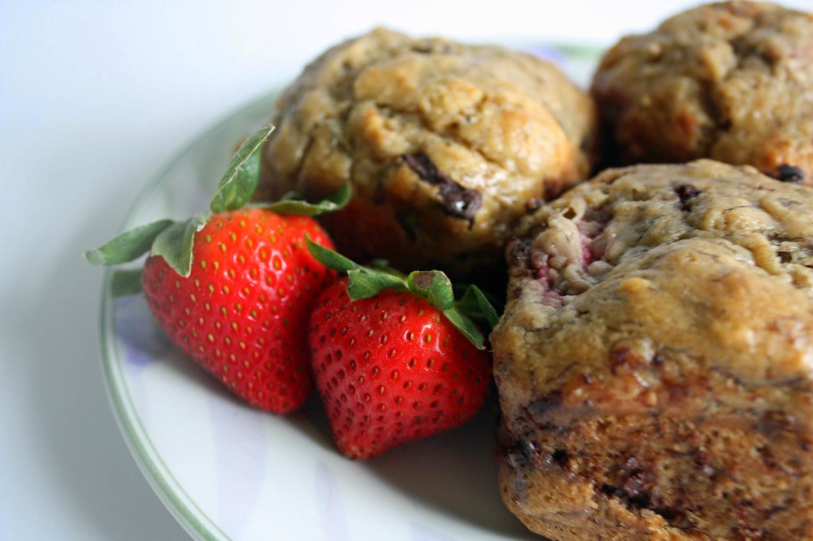 dark chocolate chunk strawberry banana bread muffins with strawberries as garnish so pretty