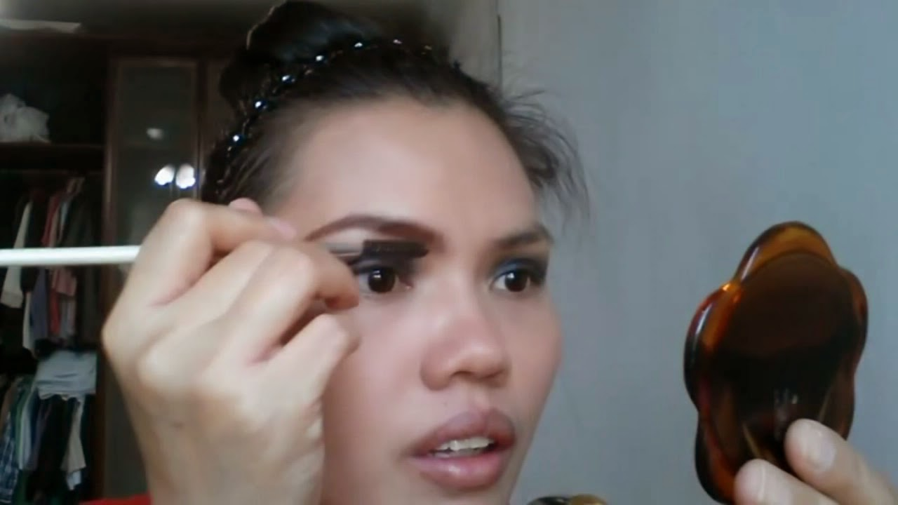 Black Smokey Eyes Makeup Tutorial. Lady putting makeup on her eyes.
