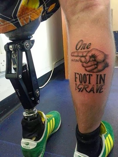 "Photo of two lower legs, left leg is a prosthetic. Right leg has a tattoo with a finger pointing to the left leg, words that say ""One Foot In The Grave"""