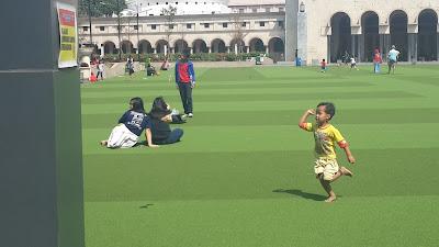 seorang anak dengan ceria berlari bermain di alun alun bandung