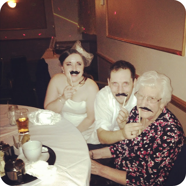 bride and groom using moustache sticks