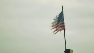 High definition stock video footage of two torn American flags wrapped together in the wind.