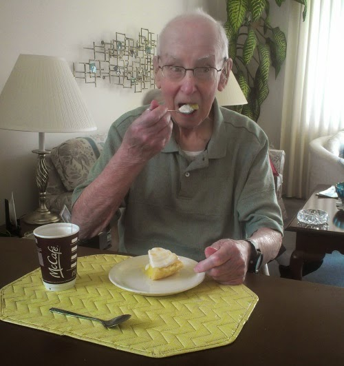 an old man--my grandfather--raising a fork to his mouth. A plated slice of lemon meringue pie sits on a yellow placemat in front of him.