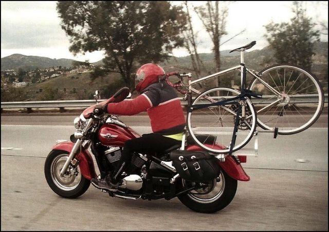 Homem levando bicleta na moto