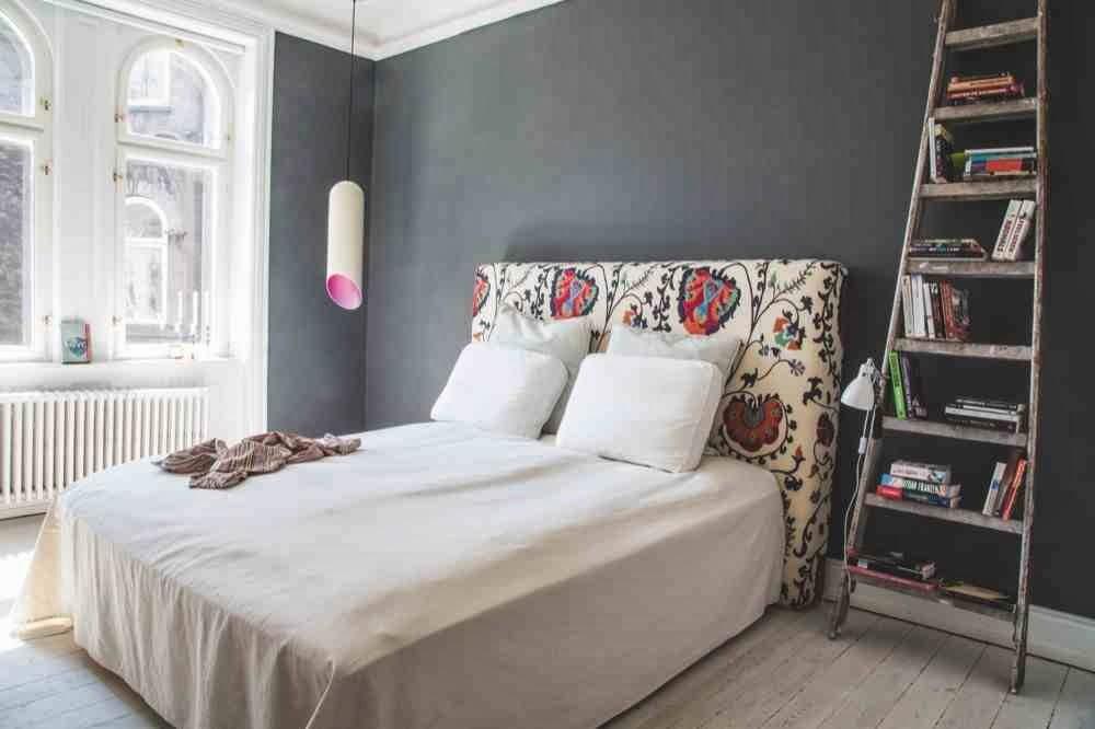 Szara ściana w sypialni, drabina drewniana jako stolik i szafka nocna, eklektyczne wnętrze