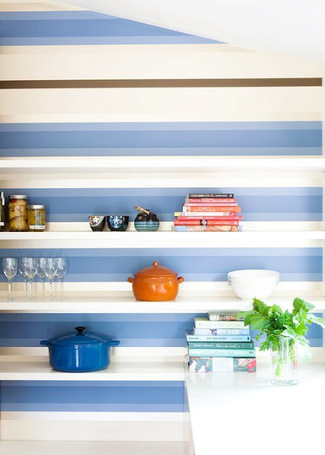 close up of kitchen with blue and white stripped backsplash with white floating shelves