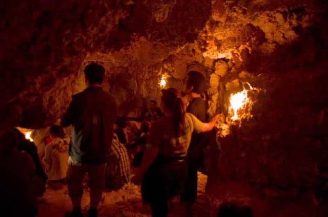 people inside candle lighted cave