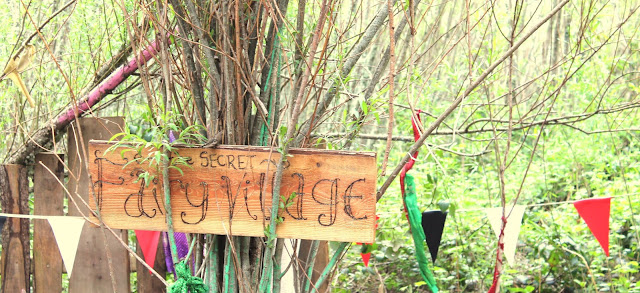 Secret fairy village in woods with colourful bunting