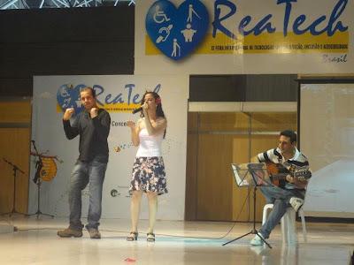 Sara canta no palco da feira, acompanhada por Gustavo França no violão e Fabiano Campos, intérprete de Libras