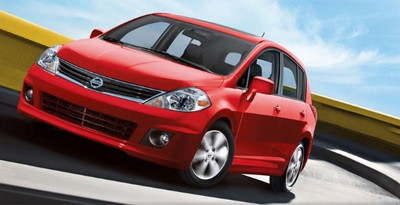Front 3/4 view of red 2011 Nissan Versa driving
