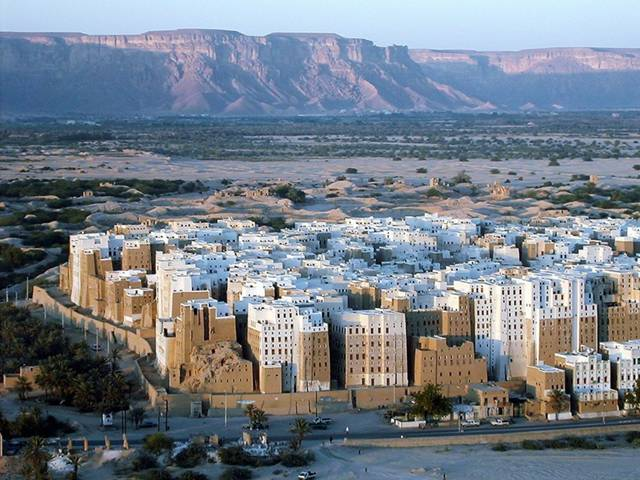 "The city of Shibam, located in the central-western area of Hadhramaut Governorate, in the Ramlat al-Sab`atayn desert, is best known for its towering mudbrick skyscrapers. This small town of 7000 is packed with around 500 mud houses standing between 5 and 11 stories tall and reaching 100 feet high, all constructed entirely of mud bricks. The bizarre skyline that the high rise buildings bestow upon the city has earned Shibam the moniker ""Manhattan of the Desert."""