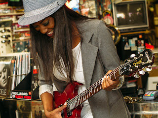 young long-haired black woman in gray suit jacket and matching hat plays a red electric guitar in a record store