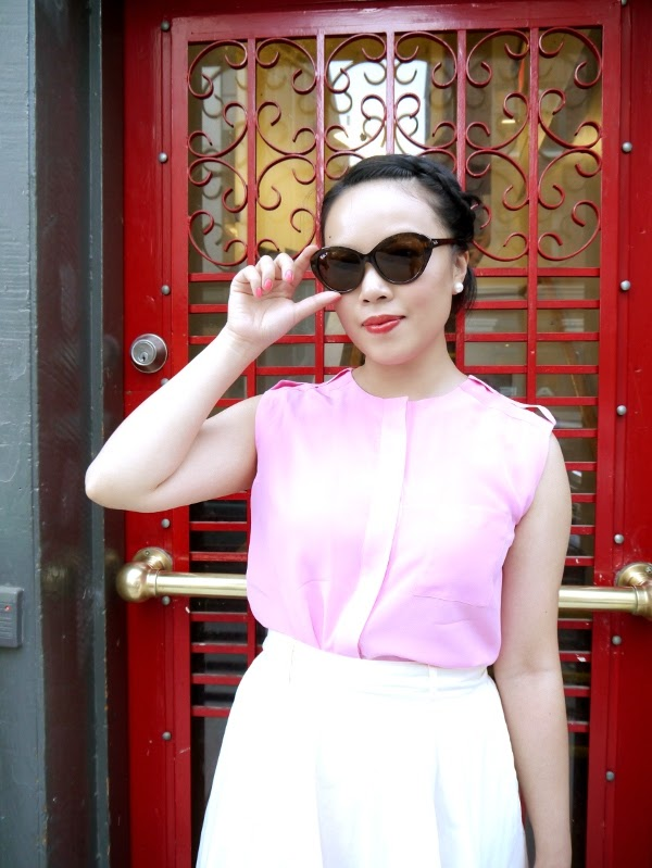 Cat-eye shades, pearl earrings, pink silk sleeveless blouse