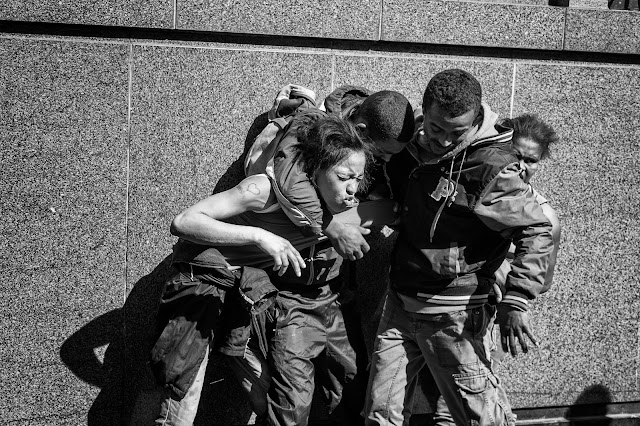 A group of people involved in a tussle in this Cape Town street photograph