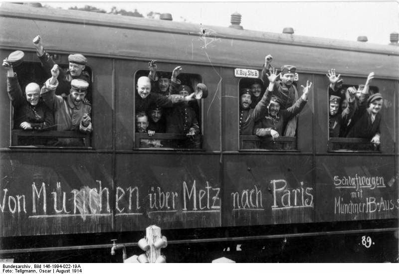 Train car with men crowding the windows and waving