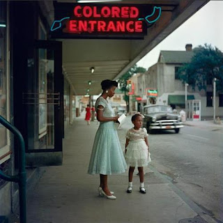 """Image of African American woman and child underneath a sign which says, """"Colored Entrance."""""""