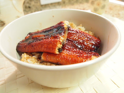 Two pieces of broiled eel on top of rice