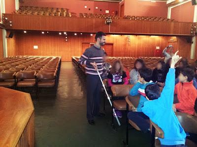 Ο Βαγγέλης Αυγουλάς περιφέρεται στο αμφιθέατρο και δείχνει στα παιδιά πως χρησιμοποιεί το Λευκό Μπαστούνι