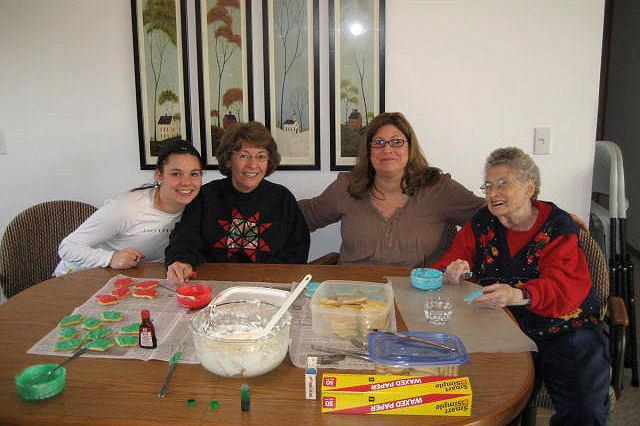Four generations decorating Christmas cookies.