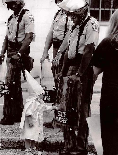 The child of a KKK member touches his reflection in an African American police officer's riot shield during a demonstration. [1992] - The 63 Most Powerful Photos Ever Taken That Perfectly Capture The Human Experience