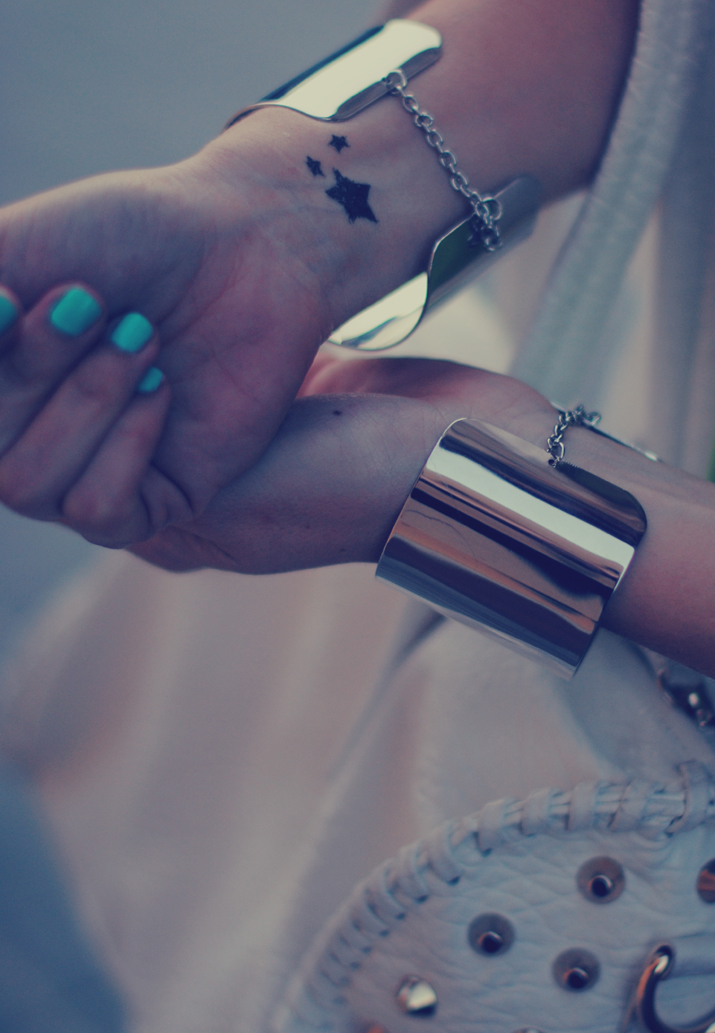 Silver bracelets like cuffs and studded bag in a fashion blog