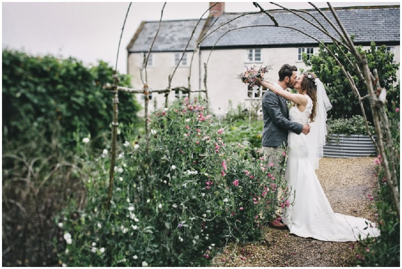 Bride and groom kissing at River Cottage HQ in Devon