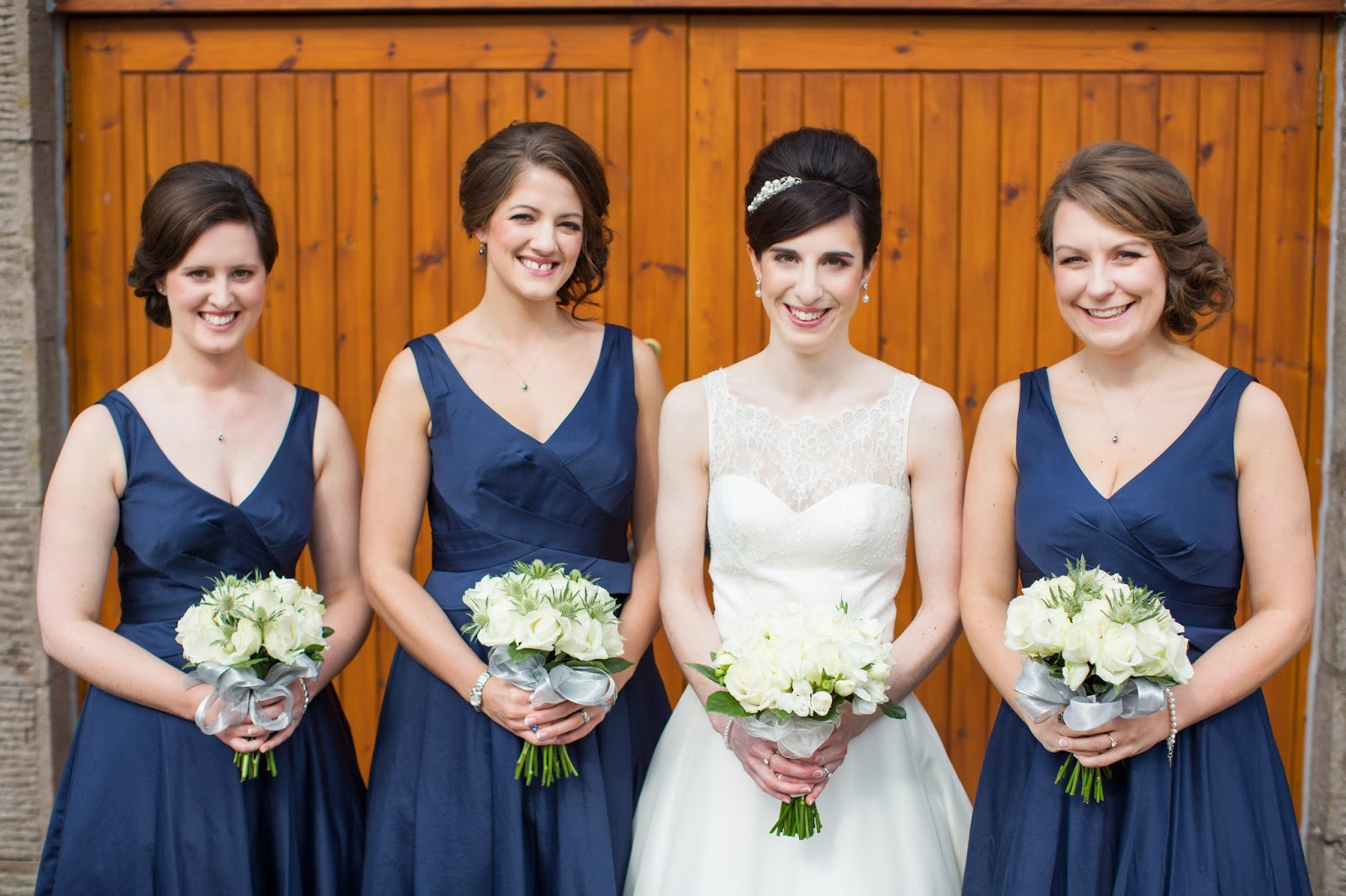 the bride and her bridesmaids all smile for a photograph after the wedding ceremony