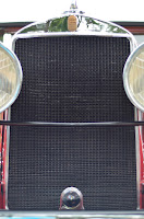front view of a vintage vehicle with grill and headlights