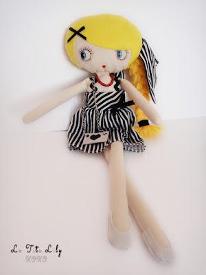 Muñeca de trapo con vestido y bolso.