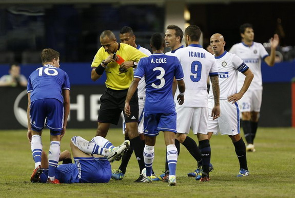 The referee puts back his red card while Chelsea player John Terry lies injured on the pitch