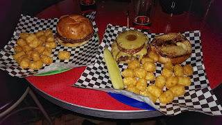 Two cheeseburgers with tater tots in baskets on a red table at a bar in St. Paul, Minnesota