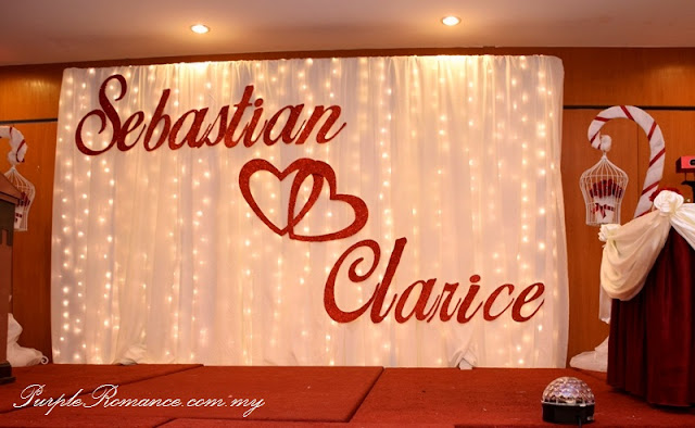 Photo booth backdrop decoration, stage backdrop, fairy lighting, bird cages, wishing tree, logo, love, maroon, ivory, satin fabric, draping, red carpet, indian, chinese, sarawakian, red roses, pearls, candle, floating candles, teddy bear, couple, love corner, scallop draping, wishing tags, spotlights, cocktail table