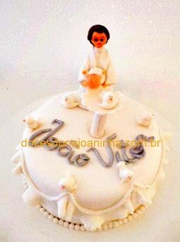 Bolo decorado com padre batizando Bebê pia batismal pombinhas e babadinhos o nome do bebê em prata
