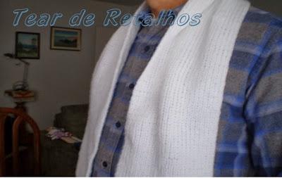 Vista de perfil do cachecol branco de tricô manual sendo usado.