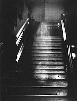 old black and white photo of stairs with translucent figure
