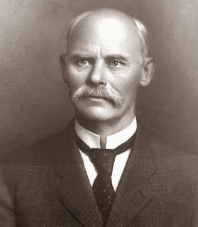 George Howard, a balding white man in a suit. Black and white photo.