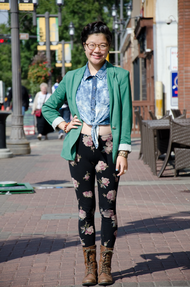 University of Alberta in Edmonton student wears a green blazer with a tie dye blue denim shirt and floral print leggings and brown combat boots.