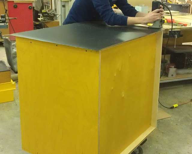 Once the laminate has been applied, what hangs off the edge of the box must be cut.  A young man in a dark blue long sleeved shirt is using a router - black cylinder with a sharp silver rotating bit - to cut off the excess black laminate from the yellow box.