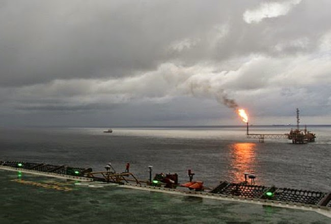 Storm clouds gather as gas is flared at an oil rig off the coast of Nigeria. (Credit: Swandau via Wikimedia Commons) Click to Enlarge.