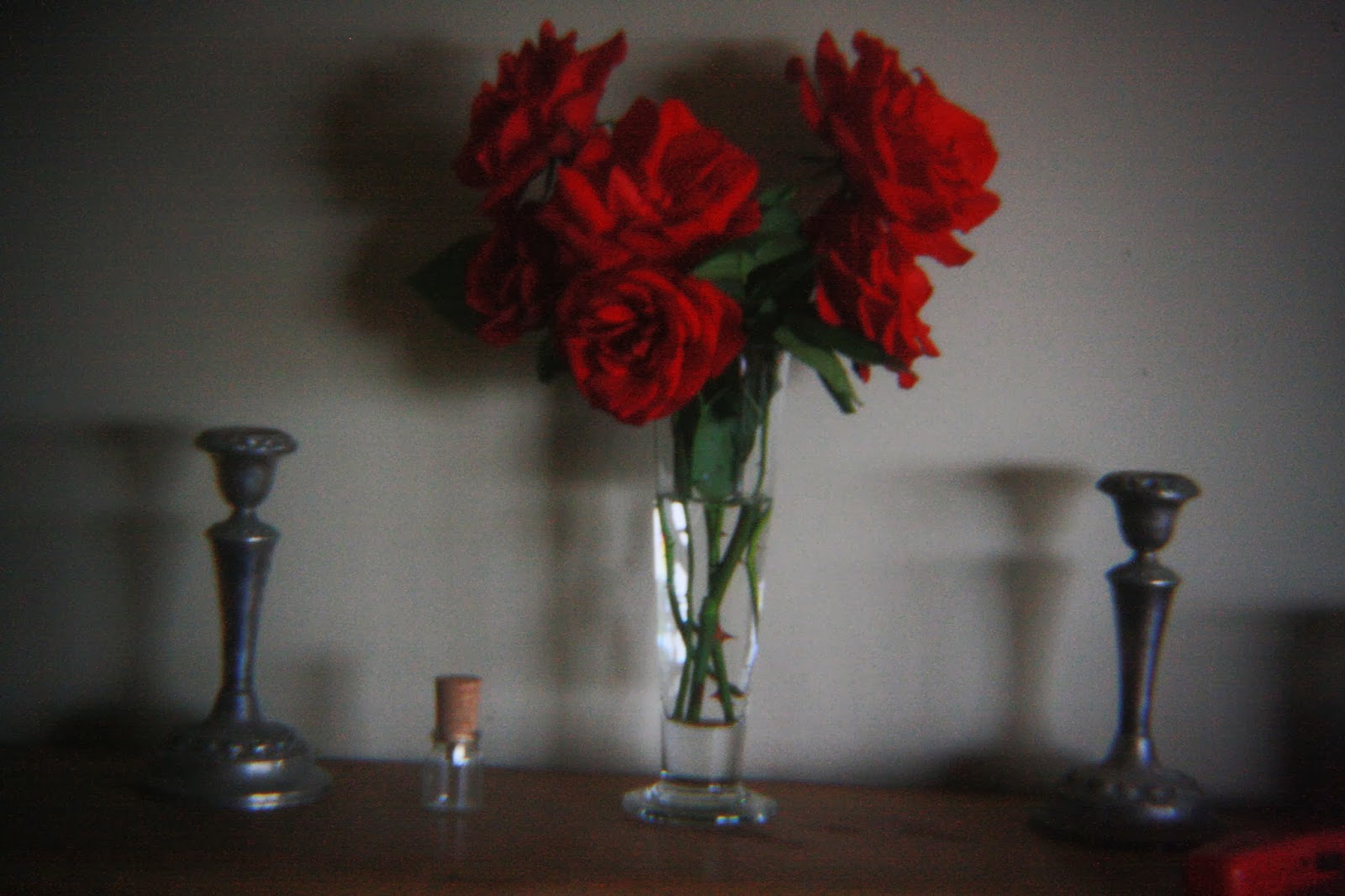 Red roses on a mantle piece.