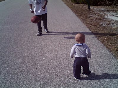 Baby walking with brother.